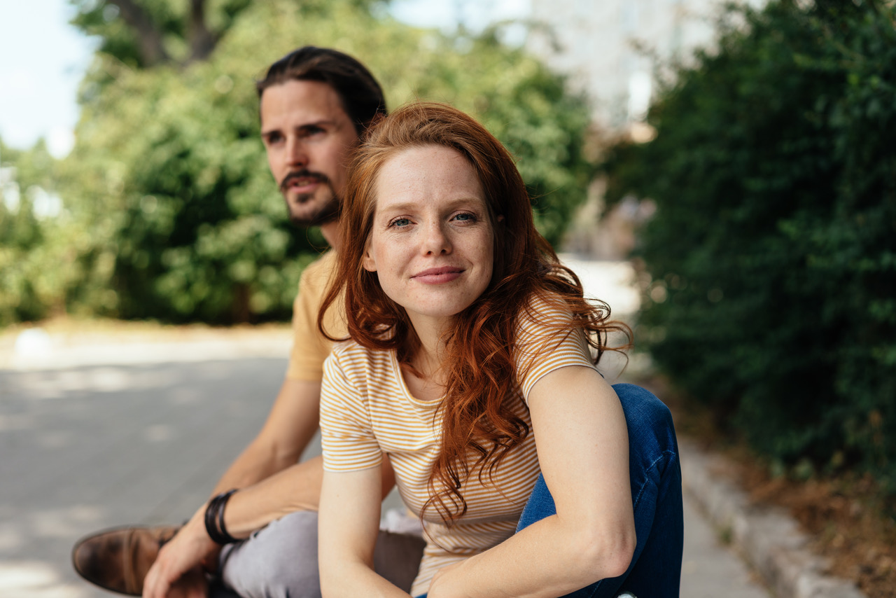 Young woman leaning towards the camera with an attentive expression and friendly smile outdoors with her boyfriend